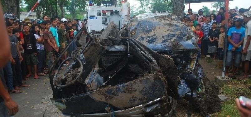 Petugas mengevakuasi mobil jenis Suzuki Carry bernomor polisi Z951W yang tertabrak Kereta Api Pasundan Jurusan Bandung–Surabaya, di perlintasan rel tanpa palang pintu di Kampung Sindangkasih, Kelurahan Sukanegara, perbatasan Kecamatan Cibeureum-Purbaratu,