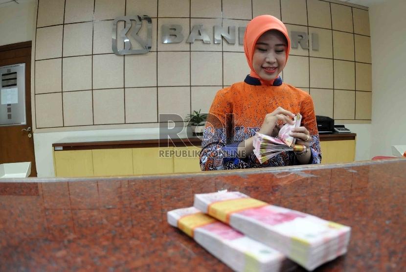 Petugas menghitung uang di banking hall Bank Rakyat Indonesia, Jakarta, Selasa (20/10).