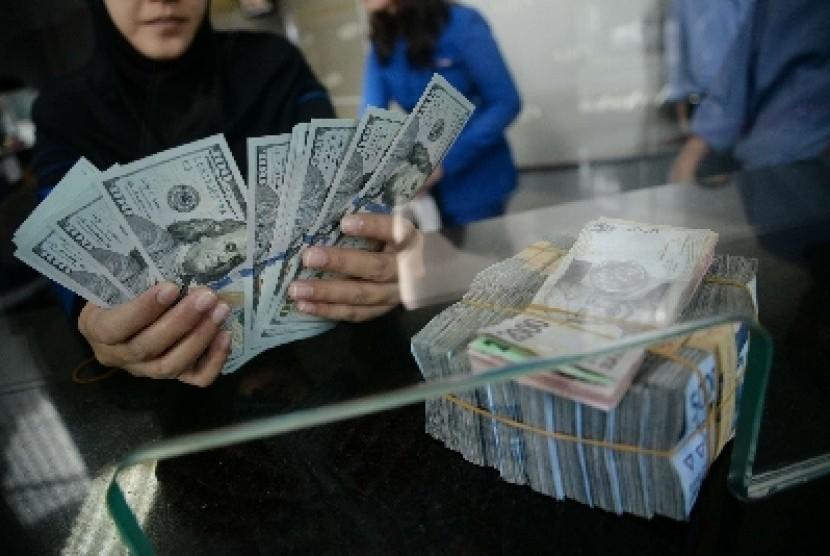 Petugas menghitung uang rupiah dan dolar di salah satu penukaran uang di Jakarta, Kamis (5/3).