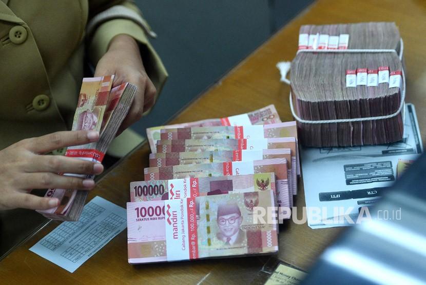 Petugas menghitung uang rupiah di salah satu gerai penukaran mata uang asing di Jakarta, Rabu (14/3).