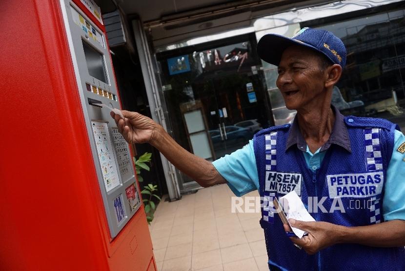 Petugas mengoprasikan mesin parkir elektronik di Jalan Pintu Air, Jakarta, Rabu (22/3).