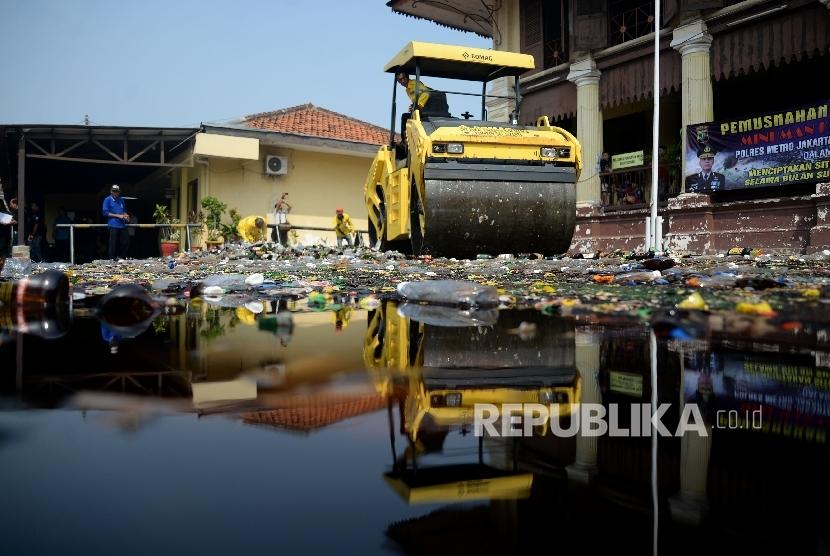 Petugas mengunakan alat berat memusnahkan barang bukti minuman keras (miras) di halaman Polsek Palmerah, Jakarta, Selasa (23/5).