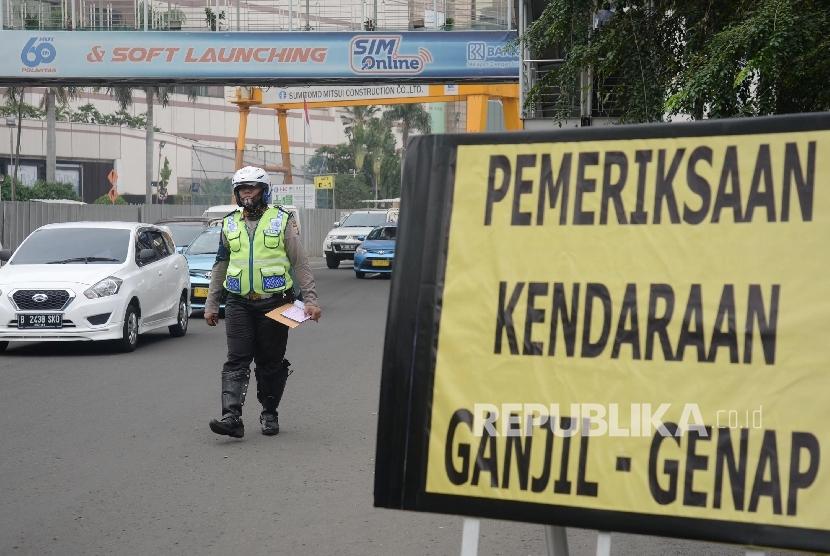 Petugas menilang pengendara mobil yang melanggar aturan pembatasan kendaraan sistem ganjil genap. ilustrasi (Republika/Yasin Habibi)