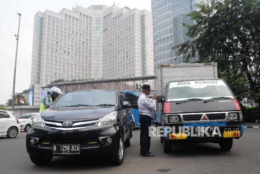 Petugas menilang pengendara mobil yang melanggar aturan pembatasan kendaraan sistem ganjil genap di MH Thamrin, Jakarta Pusat, Selasa (30/8). (Republika/Yasin Habibi)