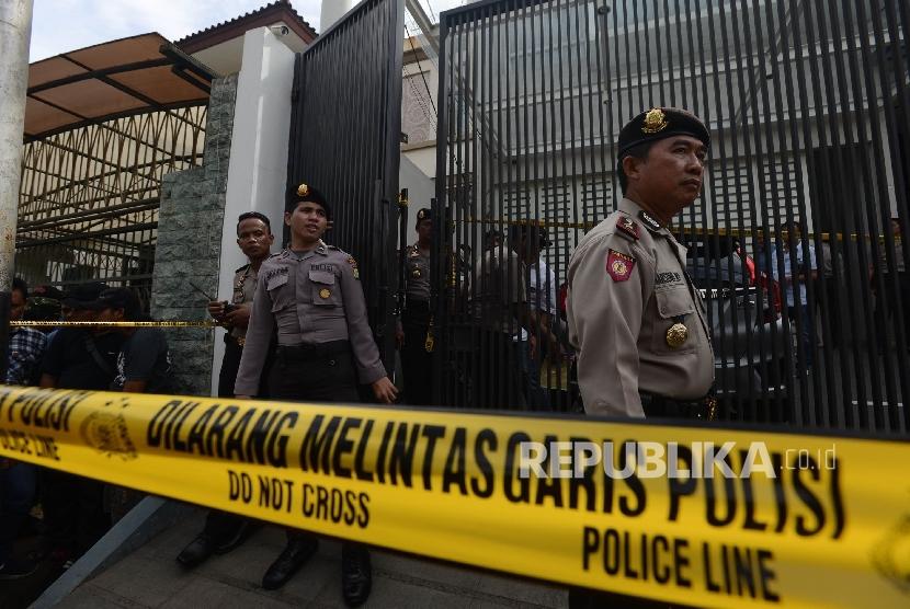 Petugas menjaga Tempat Kejadian Perkara (TKP) kasus pembunuhan sadis di Perumahan Pulomas, Pulogadung, Jakarta Timur, Selasa (27/12).