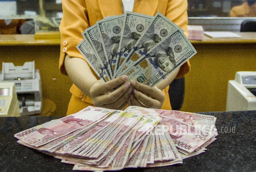 Petugas menunjukan pecahan uang dolar Amerika Serikat dan rupiah di salah satu gerai penukaran mata uang asing, di Jakarta (ilustrasi)