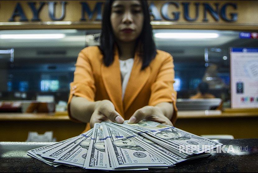 Petugas menunjukan pecahan uang dolar Amerika Serikat di salah satu gerai penukaran mata uang asing, di Jakarta. (ilustrasi)