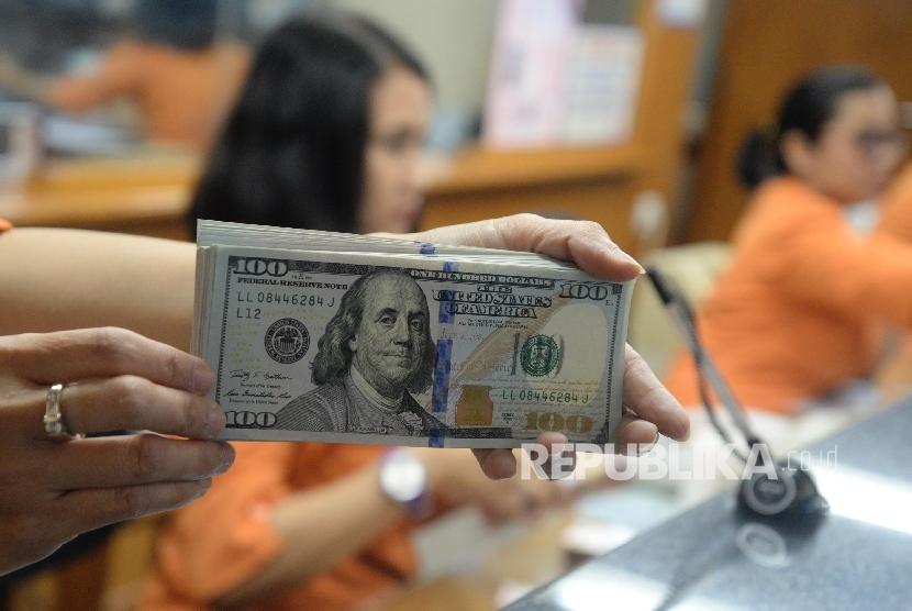 Petugas menunjukan uang dolar AS di tempat penukaran mata uang asing. ilustrasi