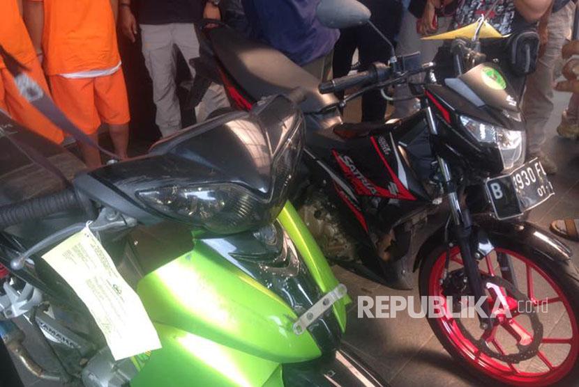 Petugas menunjukkan barang bukti dan senjata tajam pelaku aksi begal yang tergabung dalam Geng Motor AS 378 berinisial AA dan MR diamankan di Polres Metro Bekasi Kota, Selasa (11/4).