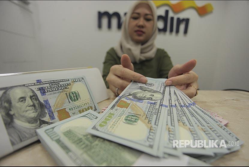 Petugas menunjukkan uang pecahan dolar AS di kantor cabang Bank Mandiri, Jakarta, Jumat (27/10). Berdasarkan data Yahoo Finance, Rupiah melemah ke level Rp13.615/USD atau tidak lebih baik dibanding sebelumnya pada  level Rp13.581/USD.