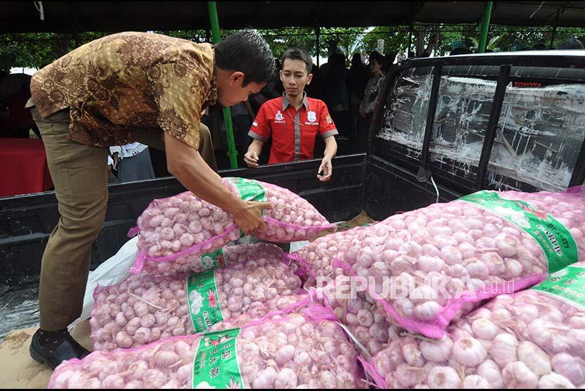 Petugas menurunkan ratusan kilogram bawang putih milik Bulog Sulawesi Tengah dari mobil pengangkut untuk dipasarkan pada pasar murah yang digelar di Palu, Sulawesi Tengah, Selasa (13/6). Menjelang perayaan Idul Fitri Bulog Sulawesi Tengah mendatangkan sekitar 20 ton bawang putih untuk selanjutnya dijual kepada masyarakat dengan harga lebih murah dibanding dipasaran guna menekan lonjakan harga bawang putih dipasaran yang menembus Rp 50.000 hingga Rp 60.000 perkilogram.