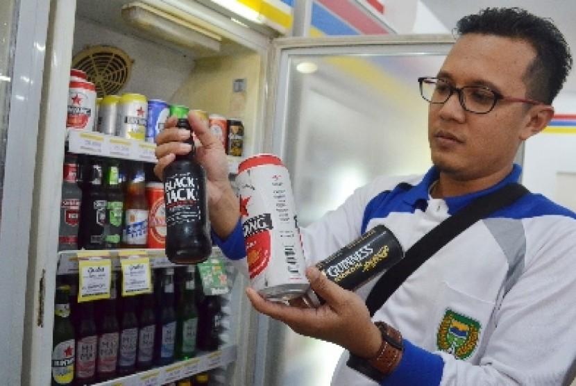 Petugas merazia minuman beralkohol yang dijual di sebuah minimarket di Kota Madiun, Jumat (30/1).