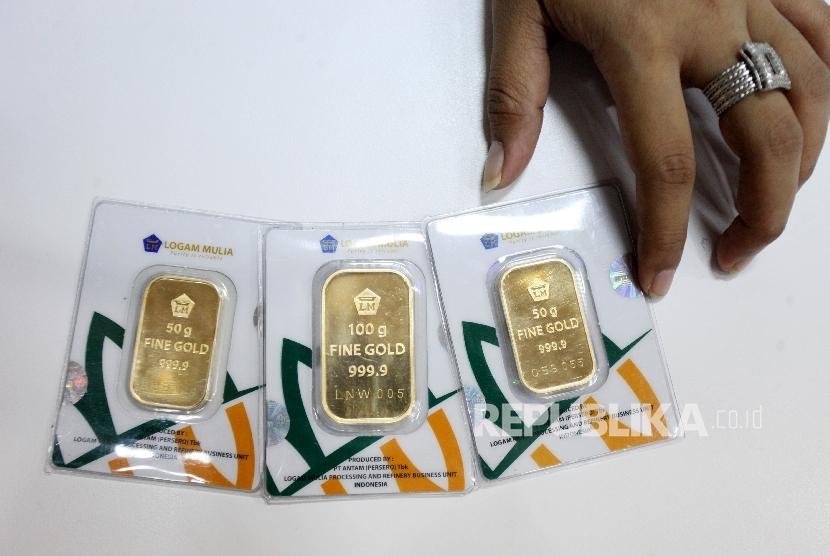 Petugas Pegadaian menujukkan logam mulia emas batangan di kantor PT Pegadaian, Jakarta, Selasa (11/7).