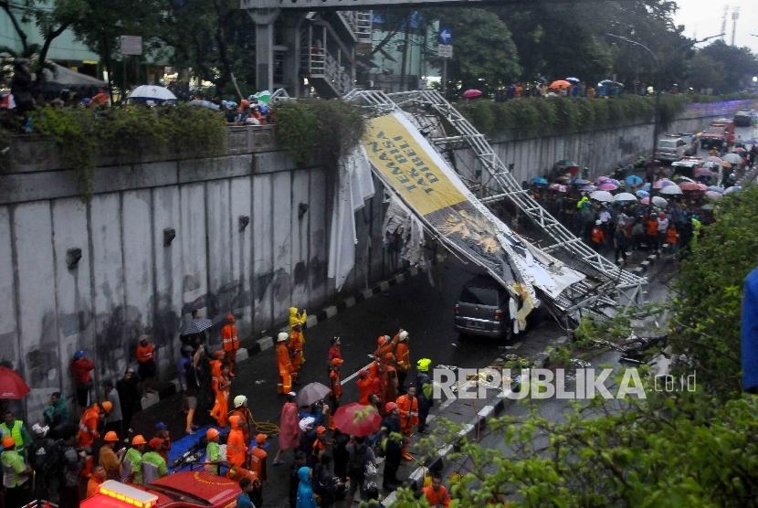 Petugas pemadam kebakaran dan Dishub berusaha mengevakuasi jembatan penyebrangan orang (JPO) yang ambruk di Pasar Minggu, Jakarta, Sabtu (24/9).
