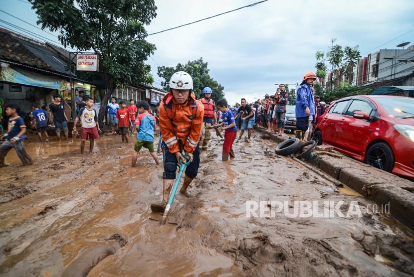 Petugas pemadam kebakaran Kota Bandung membersihkan lumpur akibat banjir bandang di Jalan A.H Nasution, Bandung, Jawa Barat, Selasa (20/3).