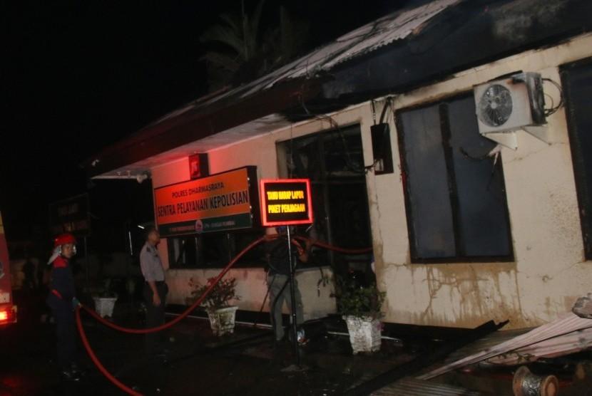 Petugas pemadam kebakaran, memadamkan api yang membakar Polres Dharmasraya, Sumatera Barat, Ahad (12/11) dini hari.