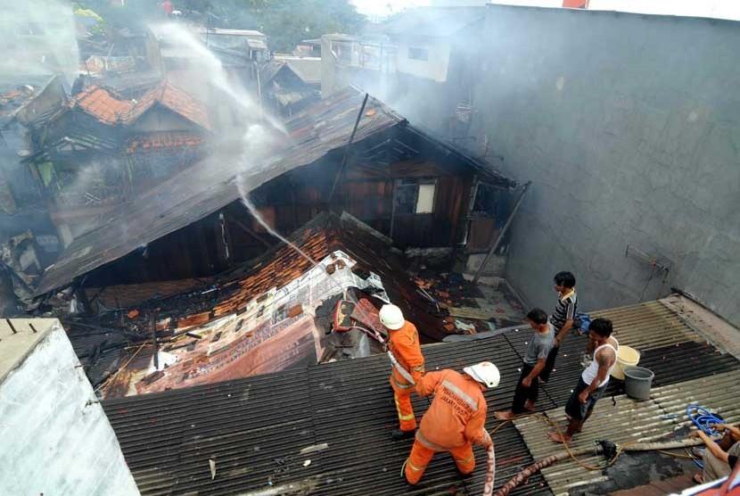 Petugas pemadam kebakaran mencoba memadamkan api saat kebaran di pemukiman padat di Kelurahan Kramat, Senen, Jakarta Pusat, Jumat (24/8). (Wihdan Hidayat/Republika)