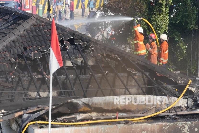Petugas pemadam kebakaran tengah menjinakkan si jago merah saat terjadi kebakaran di stasiun Klender Jakarta, Jumat (19/5).