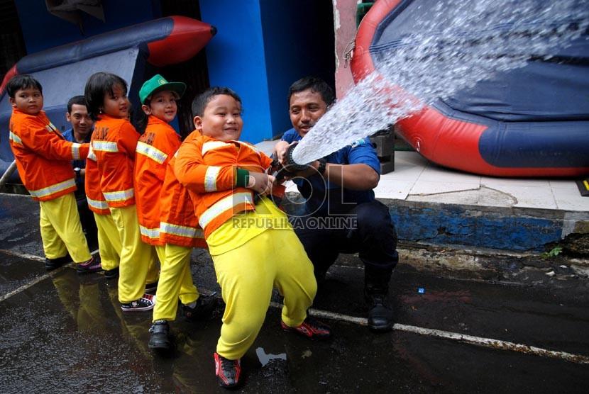 Petugas pemadam mendampingi siswa TK melakukan latihan pemadaman api saat kunjungan belajar ke markas pemadam kebakaran di Jalan Matraman Raya, Jakarta Timur, Senin (12/2).  (Republika/Prayogi)