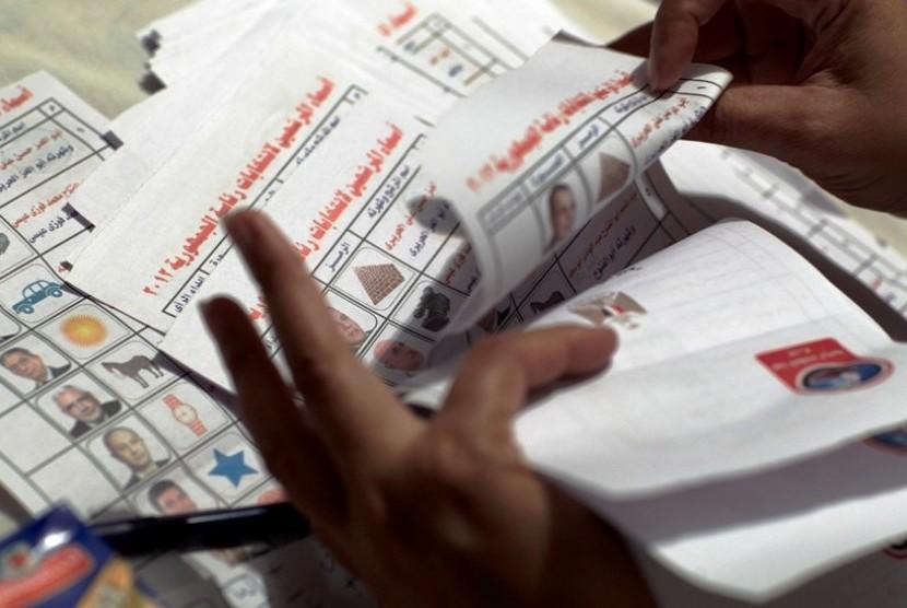 Petugas pemilu menghitung kertas suara yang berisi foto calon presiden di tempat pemungutan suara di Kairo, Mesir, Kamis (24/5).  (Fredrik Persson/AP)