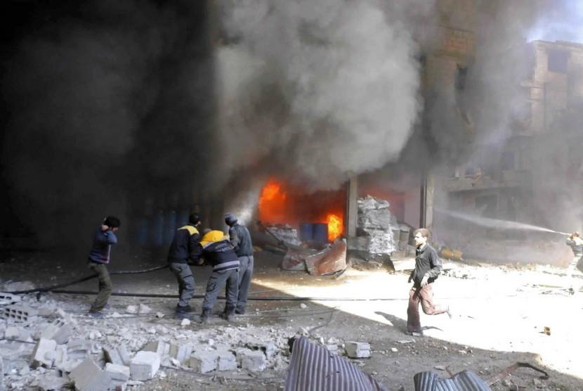 Petugas Pertahanan Sipil Suriah memadamkan api di sebuah toko yang terbakar karena serangan udara pasukan Suriah dan gerilyawan di Ghouta, pinggiran Damaskus, Selasa (20/2).