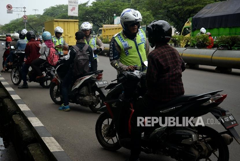 Petugas polisi melakukan penindakan terhadap pelanggar lalu lintas dengan mengunakan sistem E-Tilang saat razia kendaraan bermotor di Kawasan Kemayoran, Jakarta, Rabu (11/1).