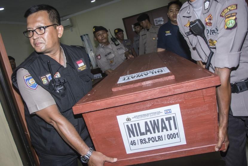 Petugas Polisi membawa peti berisi jenazah korban kebakaran pabrik kembang api seusai diserahterimakan di Posko Post Mortem di RS Polri Sukanto, Kramat Jati, Jakarta, Minggu (29/10).