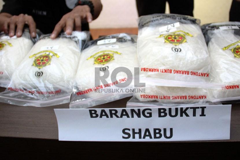 Petugas polisi menunjukan barang bukti shabu dan ekstasi senilai Rp 22 miliar di kantor Dit Narkoba Polda Metro Jaya, Jakarta Pusat, Senin (29/7).    (Republika/ Yasin Habibi)