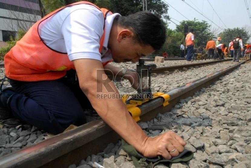 Petugas PT Kereta Api Indonesia (KAI) mengukur derajat kerataan rel kereta api di kawasan Jatinegara,Jakarta,Kamis (6/9).   (Agung Fatma Putra)