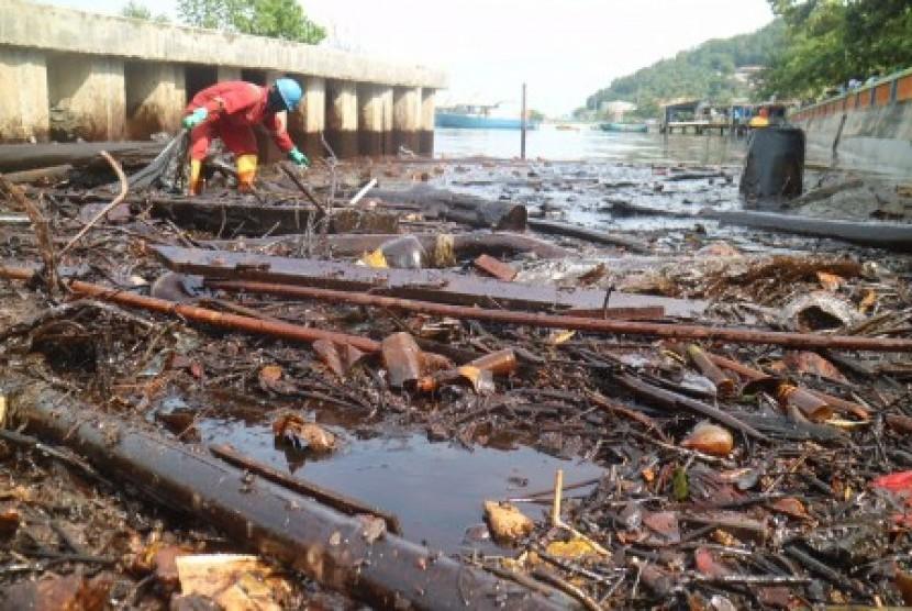 Petugas PT Pertamina membersihkan sampah yang mengandung minyak di kawasan Pesisir Melawai, Balikpapan, Kaltim, Rabu (4/4).