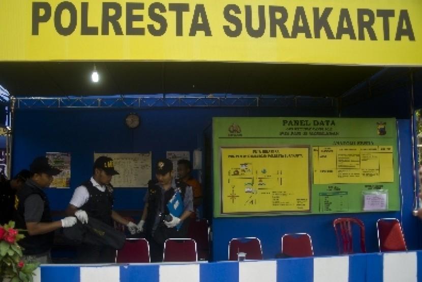 Petugas Puslabfor Polda Jateng memeriksa tempat kejadian perkara penembakan di Pos Pengamanan Lebaran Polresta Surakarta di Gemblegan, Solo, Jateng, Jumat (17/8).