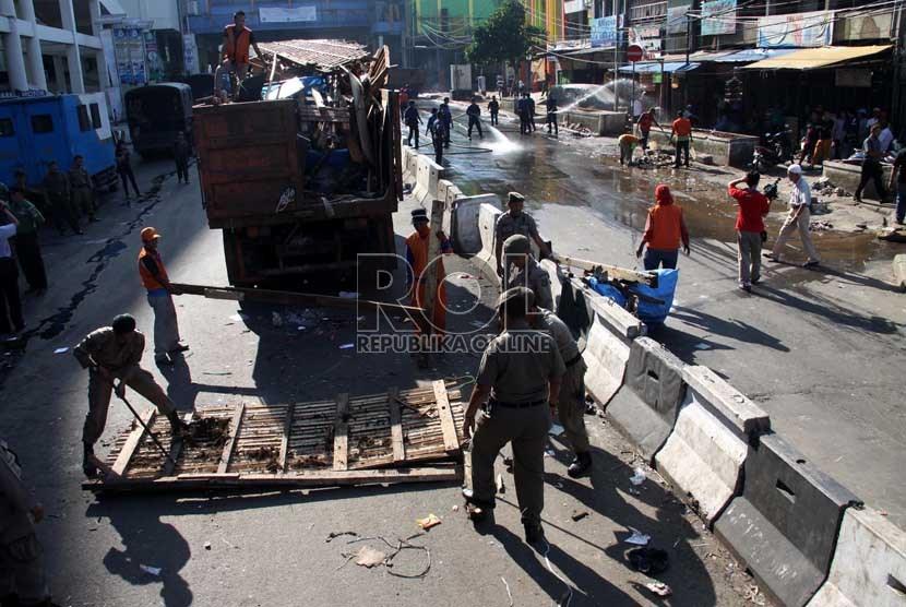 Petugas Satpol PP melakukan pembongkaran lapak PKL di kawasan Pasar Tanah Abang, Jakarta Pusat, Ahad (11/8). (Republika/ Yasin Habibi)