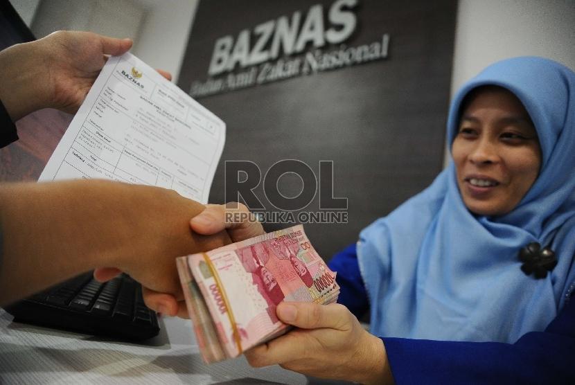 Petugas sedang melayani pembayar zakat di Baznas, Jakarta, Rabu (1/4).