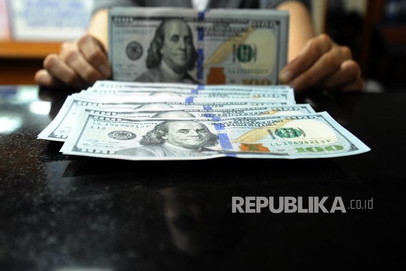 Petugas sedang menghitung mata uang dolar pada penukaran uang di Jakarta.  (Republika/Tahta Aidilla)