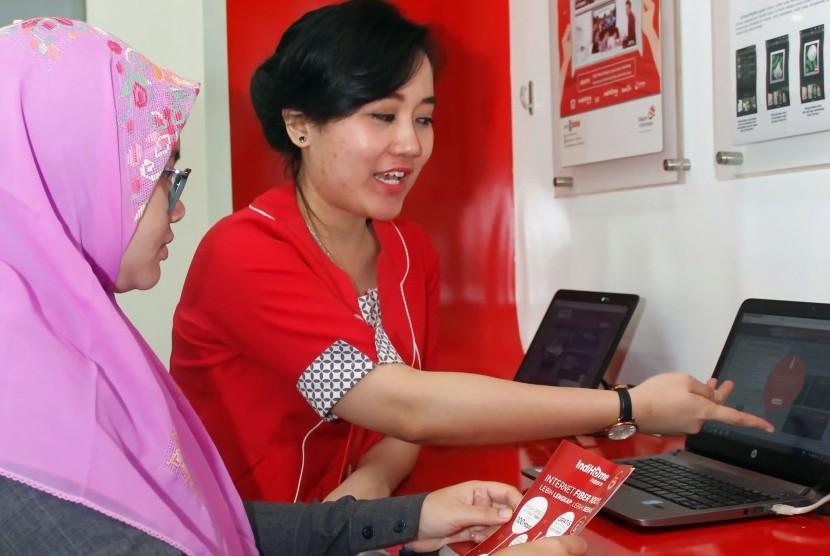 Petugas Telkom, menjelaskan layanan bundling Telepon, Internet dan IPTV atau Triple Play (3P) Indihome, di Plasa Telkom, Jakarta, Selasa (22/3).