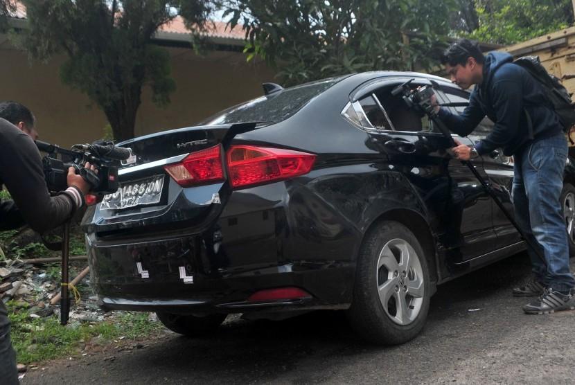 Pewarta mengambil gambar kondisi mobil yang menjadi barang bukti kasus penembakan mobil oleh polisi di Lubuk Linggau, di Mapolda Sumsel, Palembang, Jumat (21/4).