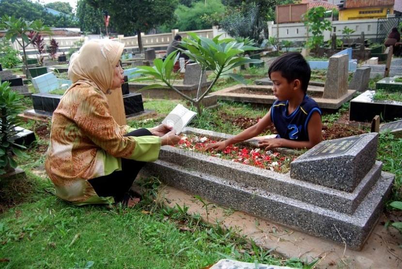 Peziarah berdoa di depan makam sanak saudaranya di kompleks pemakaman Pejaten Barat, Jakarta Selatan, Senin (23/6).