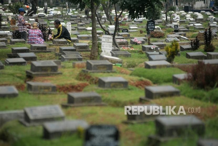 Peziarah berdoa di makam anggota keluarga (ilustrasi)
