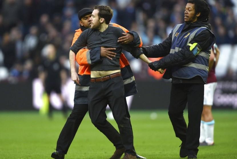 Pihak keamanan menahan seorang fan West Ham yang masuk ke lapangan Stadion London saat laga melawan Burnely, Sabtu (10/3).