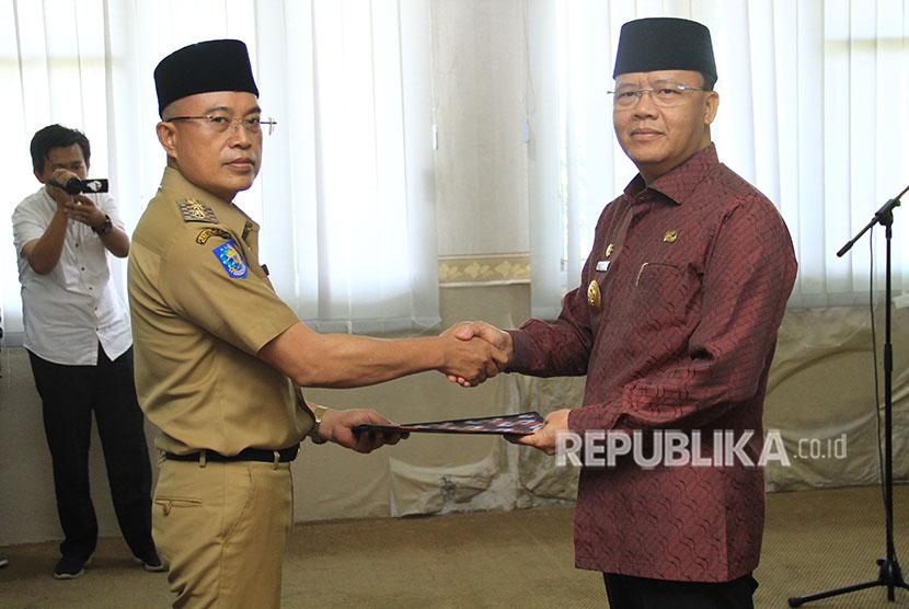 Plt Gubernur Bengkulu Rohidin Mersyah (kanan) menyerahkan SK Kemendagri kepada Wakil Bupati Bengkulu Selatan Gusnan Mulyadi (tengah) di Kantor Pemerintahan Provinsi Bengkulu, Bengkulu, Kamis (17/5).