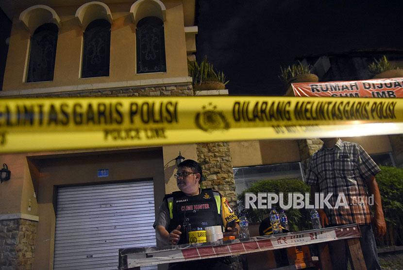 Polisi berjaga di depan sebuah rumah usai penangkapan terduga teroris di kawasan Dukuh Pakis, Surabaya, Jawa Timur, Selasa (15/5).