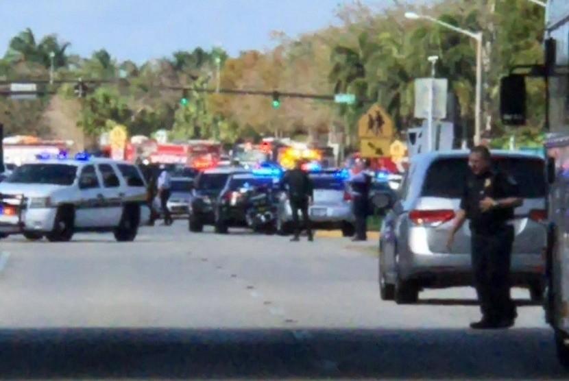 Polisi berjaga di halaman sekolah SMA di Florida yang mengalami penyerangan.