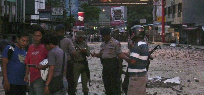 Polisi dan warga berada di lokasi bekas-bekas kerusuhan di Kota Ambon