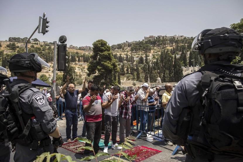 Polisi Israel berjaga-jaga saat warga Palestina melaksanakan shalat Jumat di luar Gerbang Lion di Kota Tua Yerusalem, Jumat (21/7).