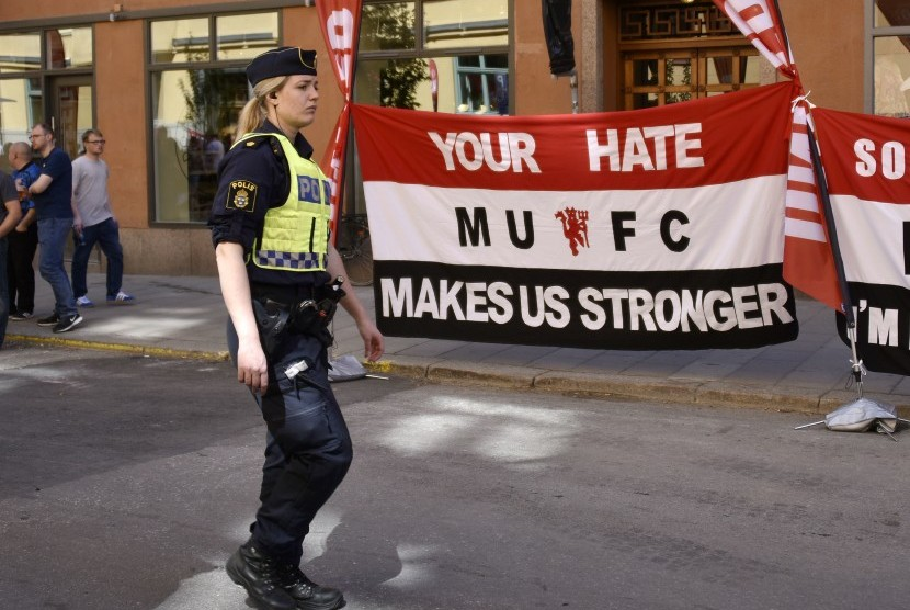 Polisi melewati spanduk penggemar Manchester United untuk para korban serangan teror bertuliskan 'kebencian Anda membuat kami lebih kuat' di jalan-jalan di Stockholm, Swedia, sebelum final Liga Europa melawan Ajax Amsterdam, Rabu (24/5).