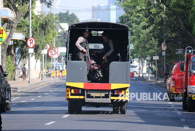 Polisi membawa sepeda motor pascateror bom di Polrestabes Surabaya, Jawa Timur, Senin (14/5).