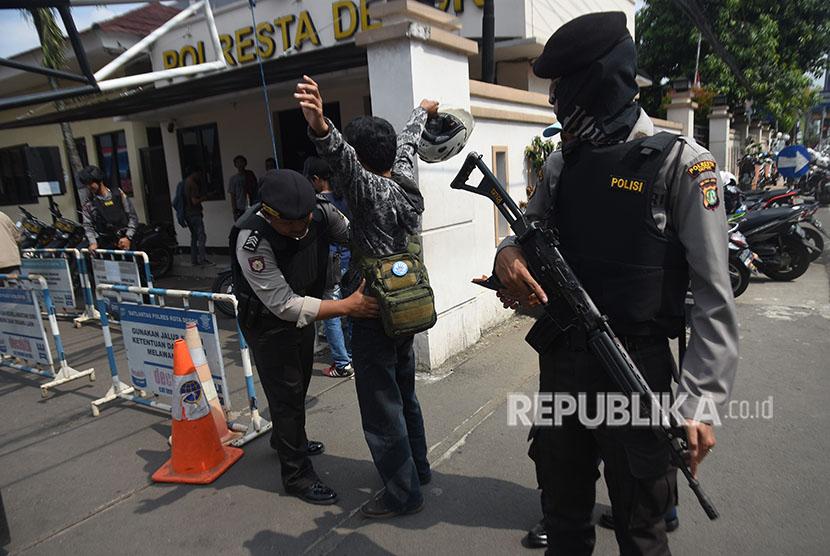[Ilustrasi] Polisi memeriksa badan dan barang bawaan pengunjung yang akan memasuki kantor polisi.
