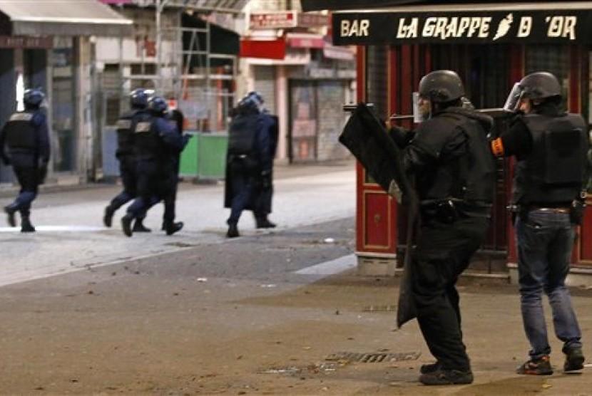 Polisi Prancis menggelar operasi memburu teroris di kawasan Saint-Denis di utara kota Paris, Rabu (18/11).  (AP/Francois Mori)