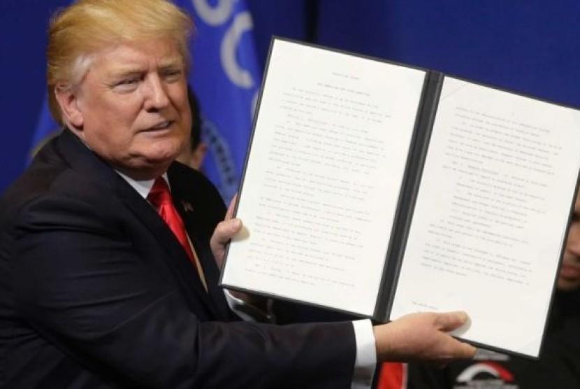 Presiden AS Donald Trump memegang kertas inpres sebelum menandatanganinya.