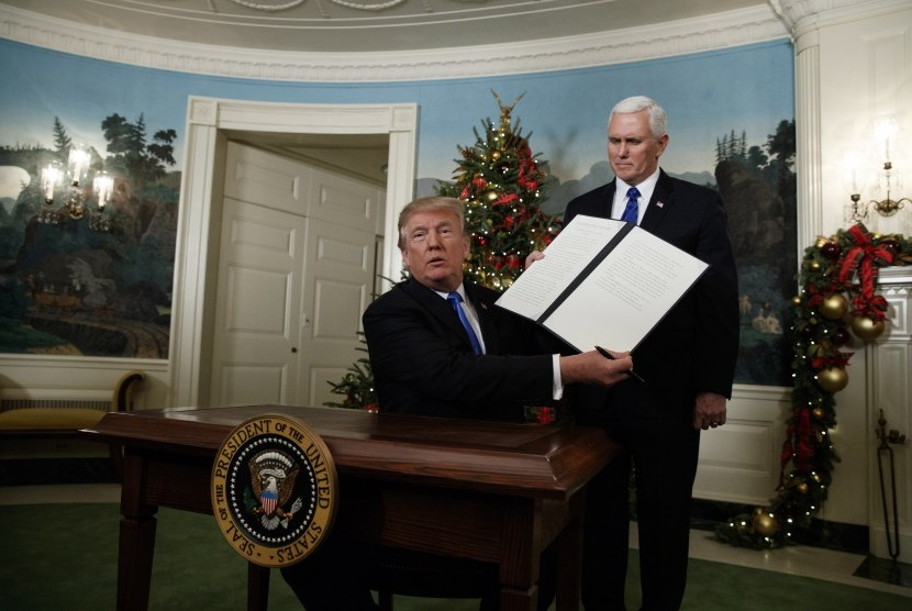 US President Donald Trump, accompanied by Vice President Mike Pence, holds up a signed proclamation recognizing Jerusalem as the capital of Israel in the Diplomatic Reception Room of the White House, Wednesday (Dec. 6), in Washington.